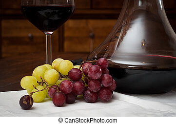 Glass of red wine served from an elegant decanter with fresh...