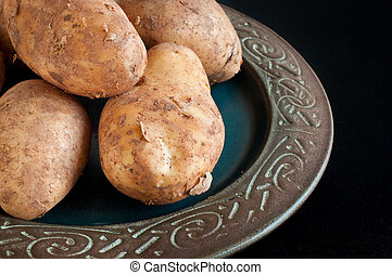 Plate of home grown potatoes piled on a rustic dish on a...