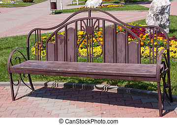 wooden bench on a background of lawn with flowers - wooden...