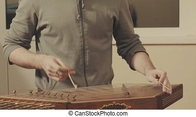 Man is playing the ethnic musical instrument - santur. Close...