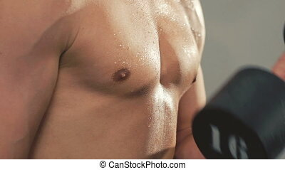 Close up man's body training with the weight in gym. Slowly.