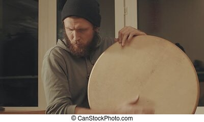 Portrait of musician playing a frame drum. Medium shot 4K