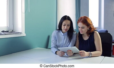 Two young women look to pad in office or cafe.