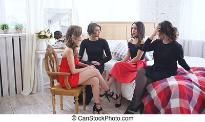 Four beautiful women have gossip talks and discuss problems while sitting on bed