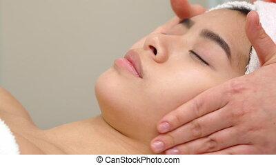 Massage specialist stokes girl's forehead - Massage...