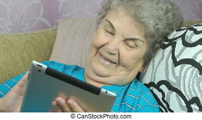 Old woman relaxes using a tablet computer at hotel room