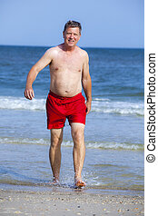 handsome man walking at the beach - handsome man in red...