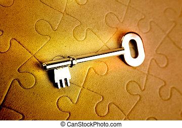 Key on puzzle - Single key resting on jigsaw puzzle