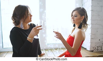 Two beautiful girls drink champagne and cheers. Women having fun laugh in bedroom