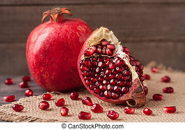 pomegranate on the old wooden board with sackcloth