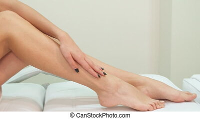 Woman strokes her leg on massage table - Slim woman stroking...