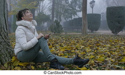Pretty woman smiling, looking up, holding a smart phone sitting on fallen leaves in autumn park