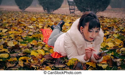 Pretty woman with attractive makeup starts talking on the phone lying on fallen leaves in autumn park.