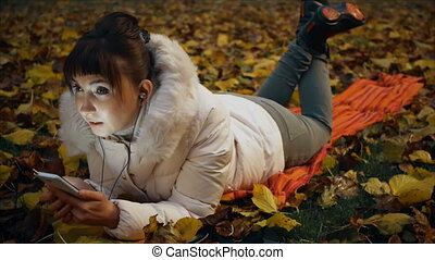 Young woman intently talking on the phone through headphones lying on fallen leaves in autumn park.