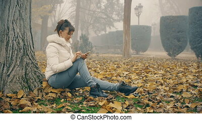 Woman writing message sitting under tree on fallen leaves in foggy autumn park