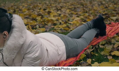 Young woman passionately talking on the phone with headphones lying on fallen leaves in autumn park.