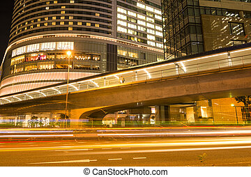 Overpass and light trail in front of building in Yokohama at...