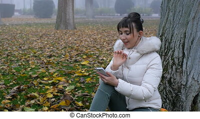 Nice woman browsing gallery on smart phone, smiling, sitting on fallen yellow leaves in autumn park.