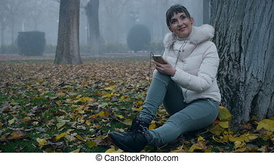 Pretty woman thinking, smiling, sitting on ground under tree in misty autumn park.