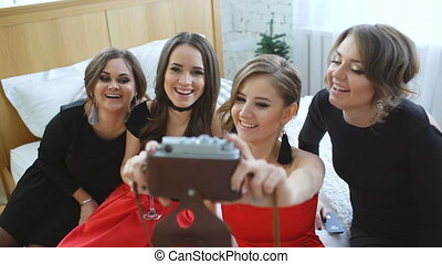young women having fun, drink alcohol and photographing selfie on retro camera at the home party