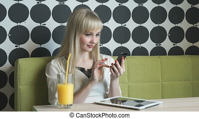 Attractive model drinking orange juice at the cafe