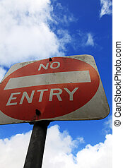 No entry sign in front of light cloudy sky.