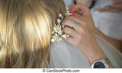 Hairdresser is finishing hairstyle for bride - Wedding hand...