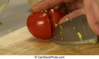 Cooker cutting off tomato pulp on cookery board - Cooker...