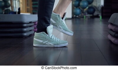 close shot sneakers legs do the exercises in a sports studio.