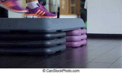 Two pairs of feet in sneakers carry out exercise on a step....