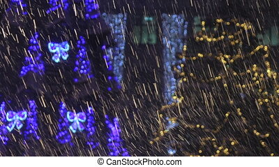 Heavy snow in spotlight - On background of Christmas...