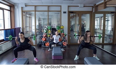 Three athletes from the sporting club squat with a barbell...