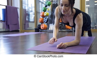Coach performs an exercise on plank with the palm of his...