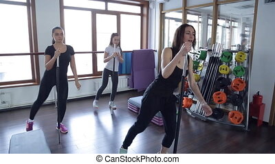 Three young women in the gym doing exercises with black...