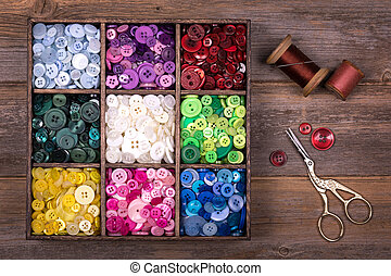 Colourful buttons with needle, thread and scissors - A box...