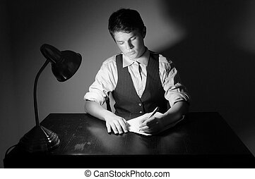Writer - A young adult man writing a letter on a desk with a...