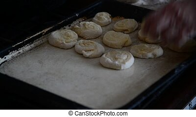 Grandma puts rolls of raw dough on baking tray - Grandma...