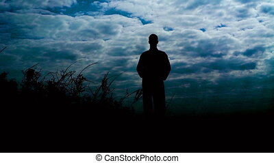 Silhouete of man stands on the stone rock with raised arms in windy day. Slowly
