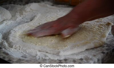 Woman lubricates butter raw dough for buns - Woman...