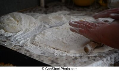 Woman rolls fancy pastry with rolling pin - Woman rolls...