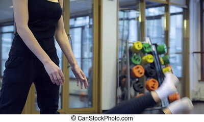 instructor helps athlete to do exercises in fitness center....