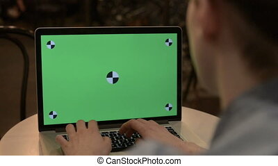 man typing on a laptop with green screen