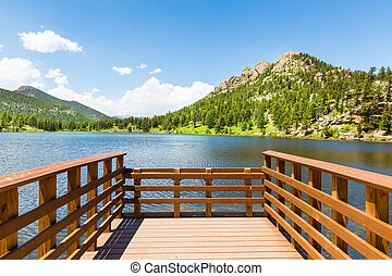 Wooden berth on lake against Rocky Mountain National Park...