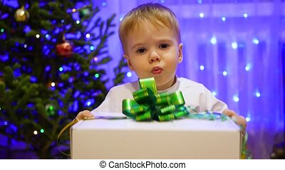 Christmas gift surprise - A kid opens present. In the background, bokeh lights and garlands.