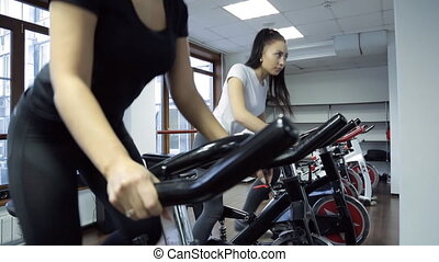 Two women doing exercise on stationary bike in fitness...