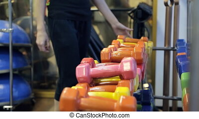 The athlete chooses dumbbells from a large set of inventory to load.