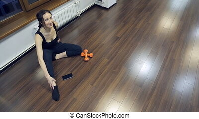 woman sitting on floor, gets up, goes to the fitness studio....