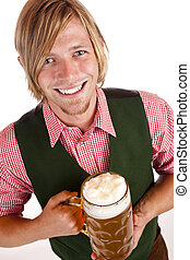 man  holds oktoberfest beer stein and looks happy into camera. Isolated on white background.
