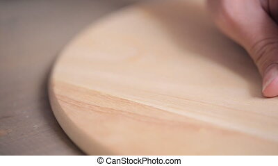 Woman hammers nail into wooden round plank on table. We see...