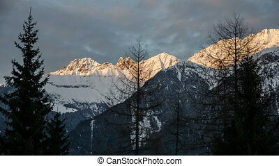 Sunset Evening Colors over Snowy Alps Mountains Time Lapse. Dolly Shot over Trees